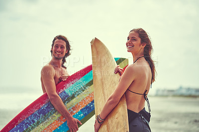 Buy stock photo Shot of a young couple spending the day out surfing