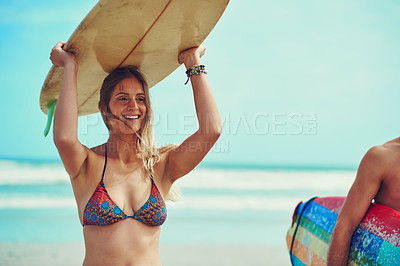 Buy stock photo Shot of a young surfer carrying her surfboard on her head