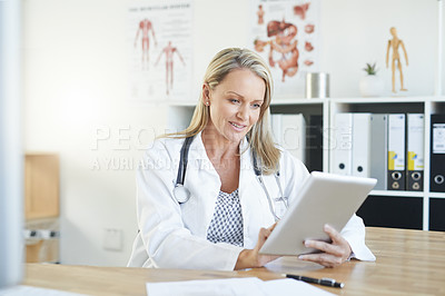 Buy stock photo Shot of a mature doctor using a digital tablet in a consulting room