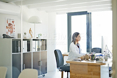 Buy stock photo Shot of a mature doctor using a computer at her desk in a consulting room