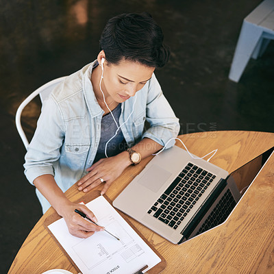 Buy stock photo Shot of a young woman doing some work in a coffee shop
