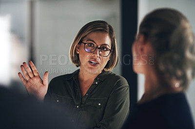 Buy stock photo Shot of colleagues having a discussion during a late night in a modern office
