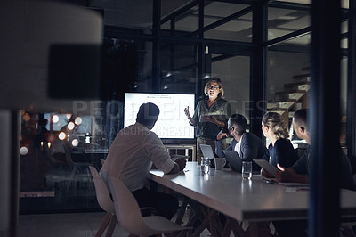 Buy stock photo Shot of a group of colleagues having a presentation during a late night in a modern office
