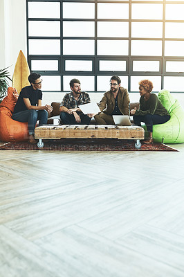 Buy stock photo Shot of a group of young designers discussing paperwork