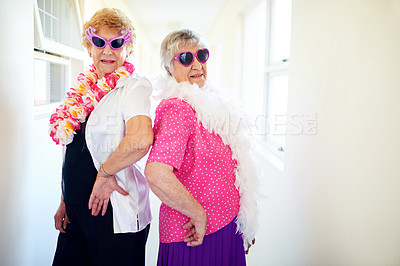 Buy stock photo Shot of two carefree elderly woman wearing sunglasses and posing for the camera inside of a building