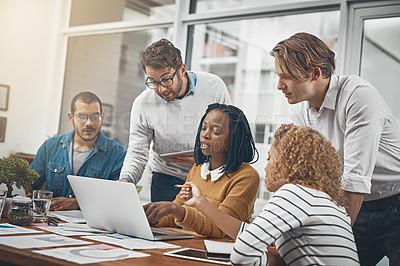 Buy stock photo Shot of a group of businesspeople looking at something on a laptop