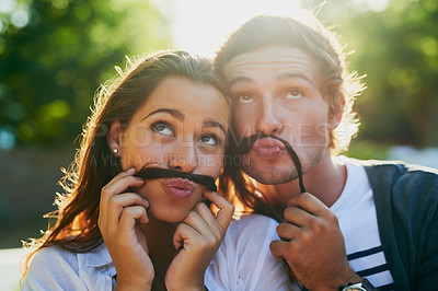 Buy stock photo Shot of a young couple enjoying a silly moment together while bonding outdoors