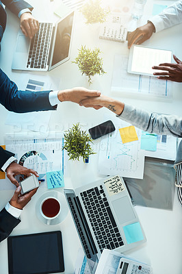 Buy stock photo High angle shot of businesspeople shaking hands in an office