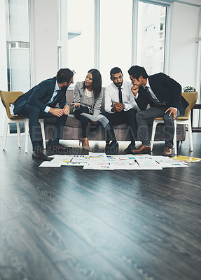 Buy stock photo Shot of businesspeople having a brainstorming session with documents spread out in front of them