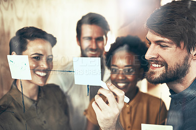 Buy stock photo Shot of a group of businesspeople brainstorming with notes on a glass wall