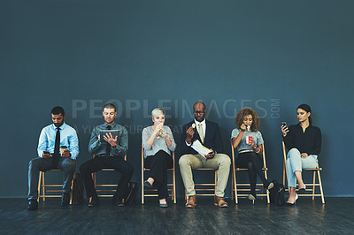 Buy stock photo Shot of a group of well-dressed business people seated in line while waiting to be interview