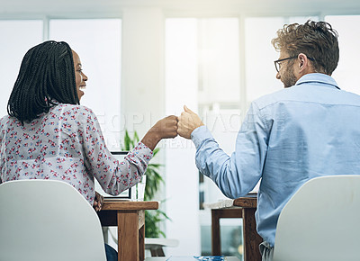 Buy stock photo Shot of two young colleagues giving each other a fist bump at their desks in a modern office