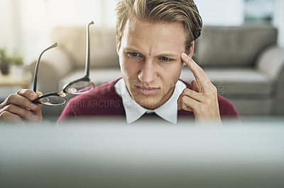Buy stock photo Shot of a young man suffering from stress while using a computer at his work desk