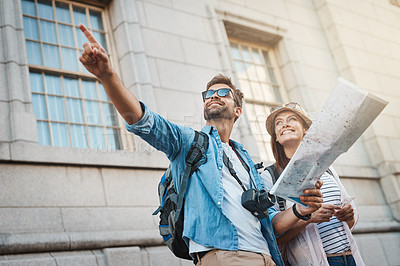 Buy stock photo Shot of a happy couple using a map while exploring a foreign city