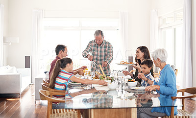 Buy stock photo Shot of a senior man carving and serving the turkey during a family lunch