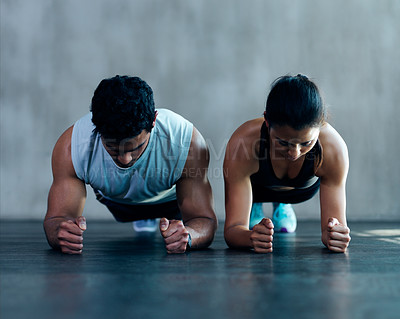 Buy stock photo Shot of an attractive young couple working out together at the gym