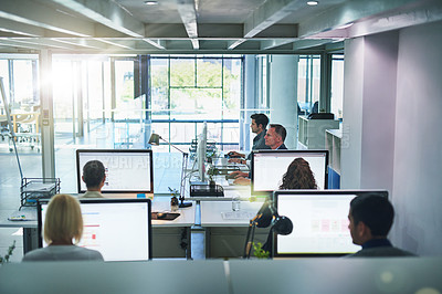 Buy stock photo Shot of corporate colleagues working together in their office