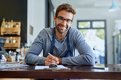 Buy stock photo Cropped shot of a handsome young coffee shop owner doing some paperwork