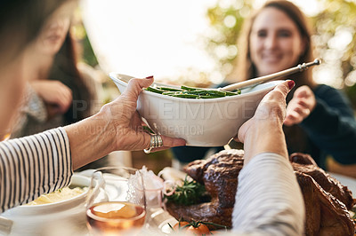 Buy stock photo Shot of a unrecognizable woman passing on a plate of green beans to a cheerful woman at lunchtime over a table