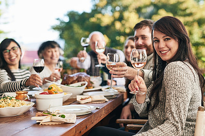 Buy stock photo Shot of a group of cheerful people raising their wine glasses to toast over a diner table while looking at the camera
