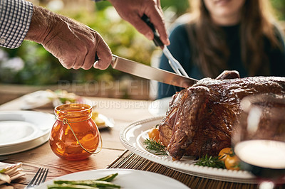 Buy stock photo Shot of a unrecognizable person cutting up a roast chicken for the other people to eat