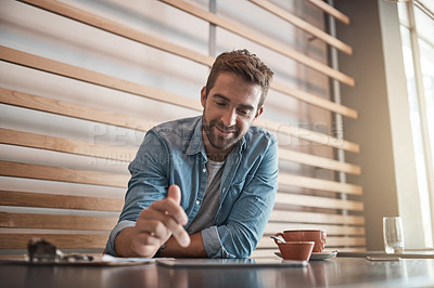Buy stock photo Shot of a handsome young man using a digital tablet in a coffee shop