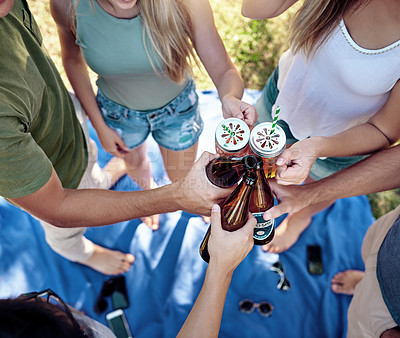 Buy stock photo High angle shot of a young group of friends toasting while enjoying a few drinks outside in the summer sun