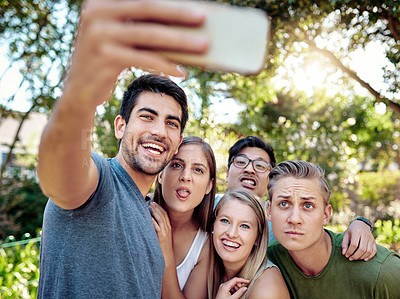 Buy stock photo Cropped shot of a young group of friends taking selfies while enjoying a few drinks outside in the summer sun