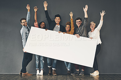 Buy stock photo Studio shot of a diverse group of people holding up a placard against a grey background