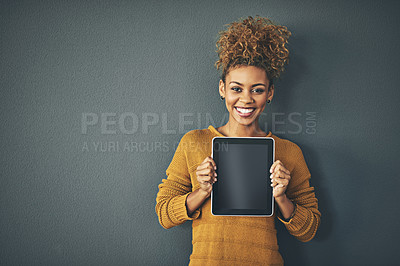 Buy stock photo Studio portrait of a young woman holding a digital tablet with a blank screen against a grey background