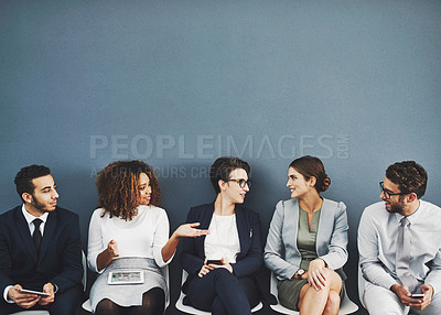 Buy stock photo Studio shot of a group of businesspeople talking while waiting in line against a gray background