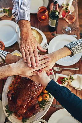 Buy stock photo High angle shot of a group of people piling their hands at a dining table