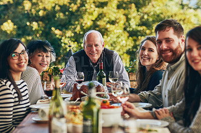 Buy stock photo Cropped shot of a group of people sitting together during a feast at a dining table