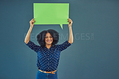 Buy stock photo Studio shot of a young woman holding up a blank speech bubble against a gray background
