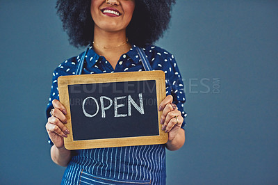 "Buy stock photo Studio shot of a young woman holding a chalkboard with the word ""open"" on it against a gray background"