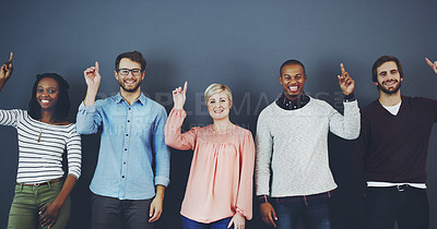 Buy stock photo Studio shot of a diverse group of people pointing upwards against a gray background