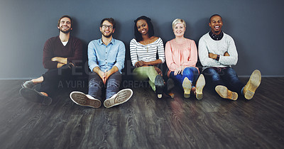 Buy stock photo Studio shot of a diverse group of people sitting together on the floor against a gray background