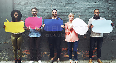 Buy stock photo Shot of a diverse group of people holding up speech bubbles against a gray brick wall