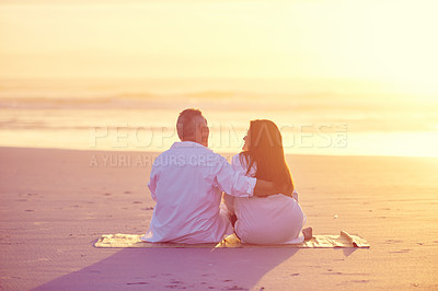 Buy stock photo Shot of a mature couple relaxing together on the beach