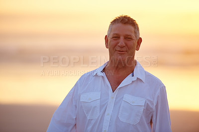 Buy stock photo Cropped portrait of a handsome mature man standing on the beach at sunset