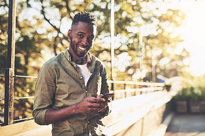 Buy stock photo Shot of a young man using his cellphone while standing outside