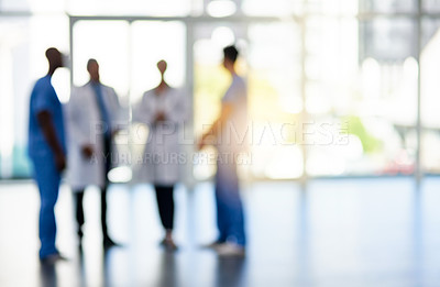 Buy stock photo Blurred shot of a team of doctors standing together in a hospital