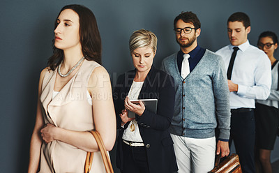 Buy stock photo Studio shot of a group of businesspeople waiting in line against a grey background