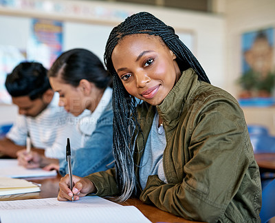 Buy stock photo Cropped portrait of an attractive young university student taking notes while sitting in class