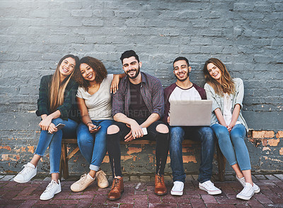 Buy stock photo Portrait of a group of young friends using their wireless devices together outdoors