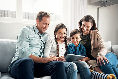 Buy stock photo Shot of a happy family using a digital tablet together at home