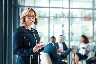 Buy stock photo Portrait of a businesswoman using a digital tablet in a modern office with her colleagues in the background