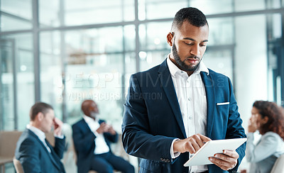 Buy stock photo Shot of a young businessman using a digital tablet in a modern office with his colleagues in the background