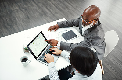 Buy stock photo High angle shot of two colleagues using a laptop together at a desk in a modern office