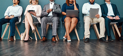 Buy stock photo Cropped studio shot of a group of a diverse group of businesspeople using wireless devices while waiting in line